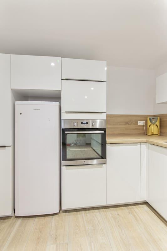 Cuisine fermée spacieuse bois et blanche avec petit coin repas | Raison Home - 7