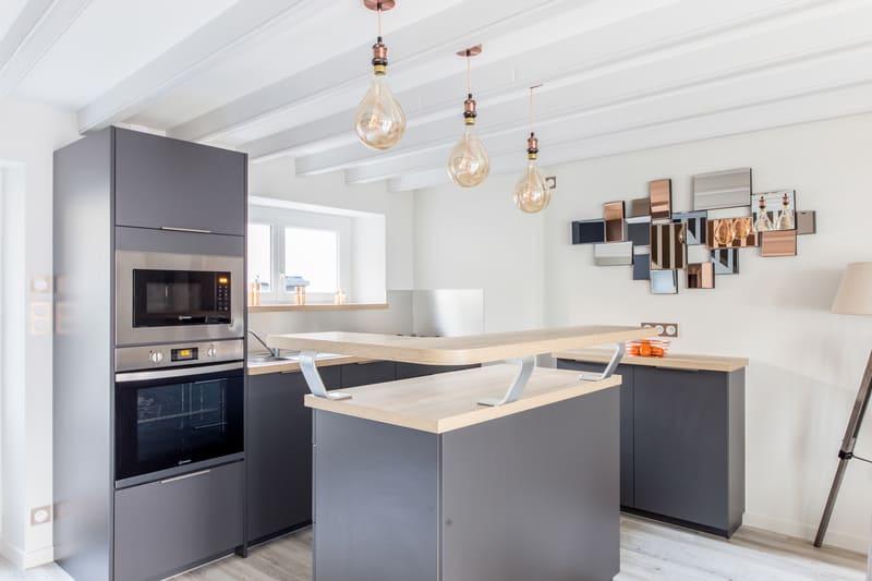 Cuisine grise et bois avec un îlot central par Romain LANGLET | Raison Home - 2