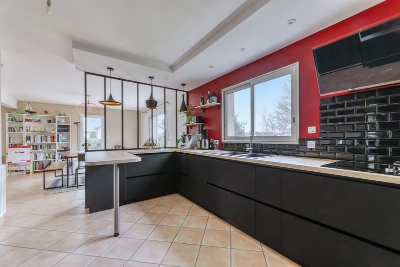 Cuisine noire bois et rouge avec coin repas et verrière par Romain LANGLET | Raison Home - 1