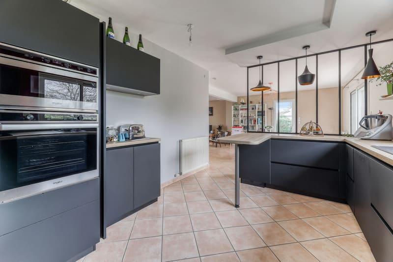 Cuisine noire bois et rouge avec coin repas et verrière par Romain LANGLET | Raison Home - 2