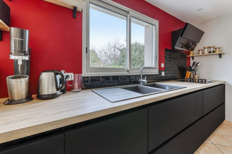 Cuisine noire bois et rouge avec coin repas et verrière par Romain LANGLET | Raison Home - 3
