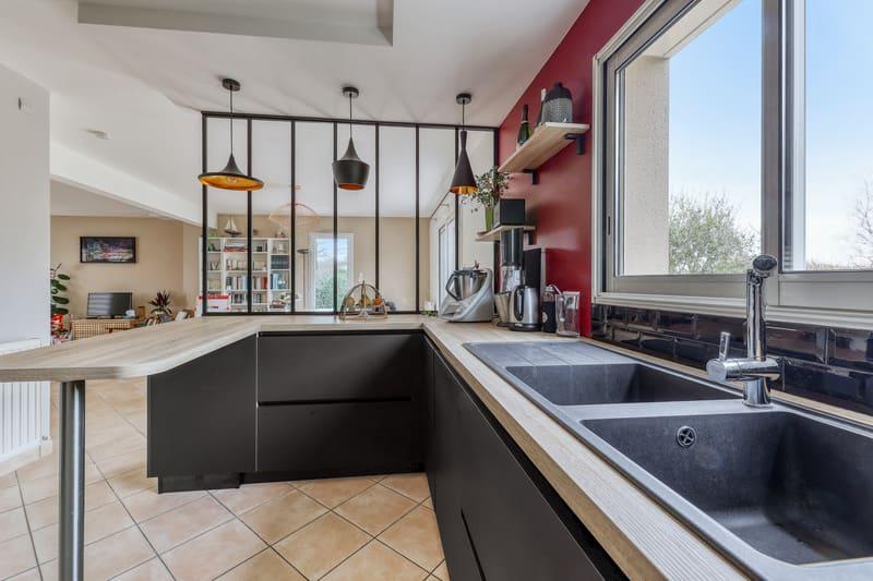 Cuisine noire bois et rouge avec coin repas et verrière par Romain LANGLET | Raison Home - 4