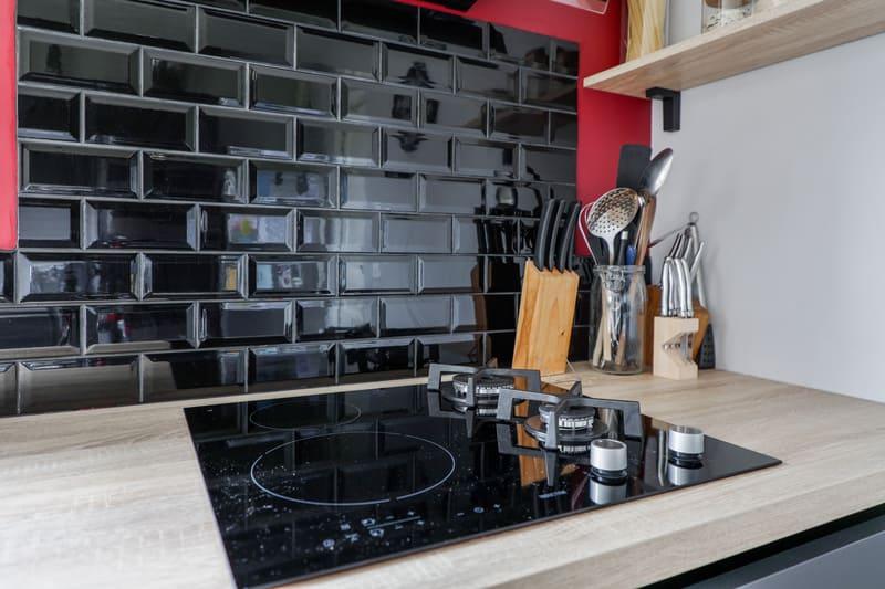 Cuisine noire bois et rouge avec coin repas et verrière par Romain LANGLET | Raison Home - 5