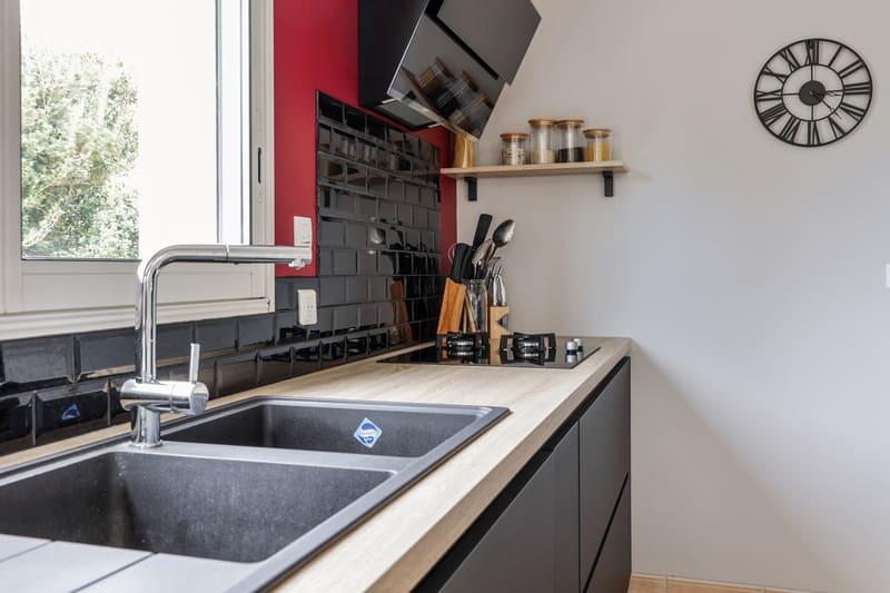 Cuisine noire bois et rouge avec coin repas et verrière par Romain LANGLET | Raison Home - 7
