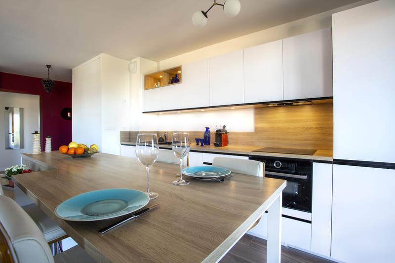 Cuisine ouverte blanc et bois avec îlot par Philippe Vacher | Raison Home - 2