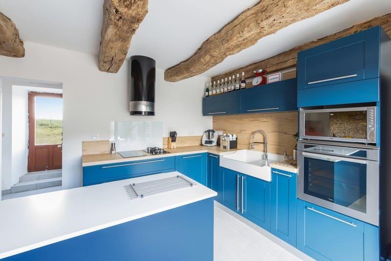 Cuisine en L blanche bois et bleue avec îlot central avec cave à vin intégrée| Raison Home - 1