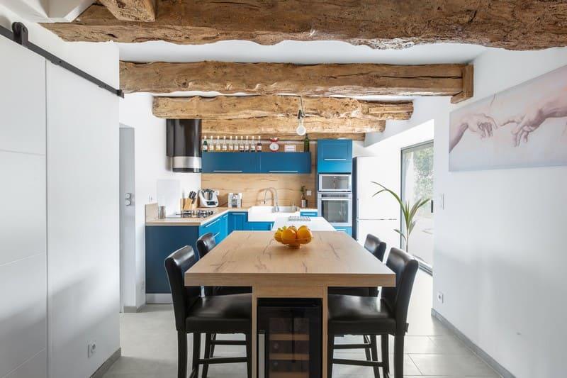 Cuisine en L blanche bois et bleue avec îlot central avec cave à vin intégrée| Raison Home - 3
