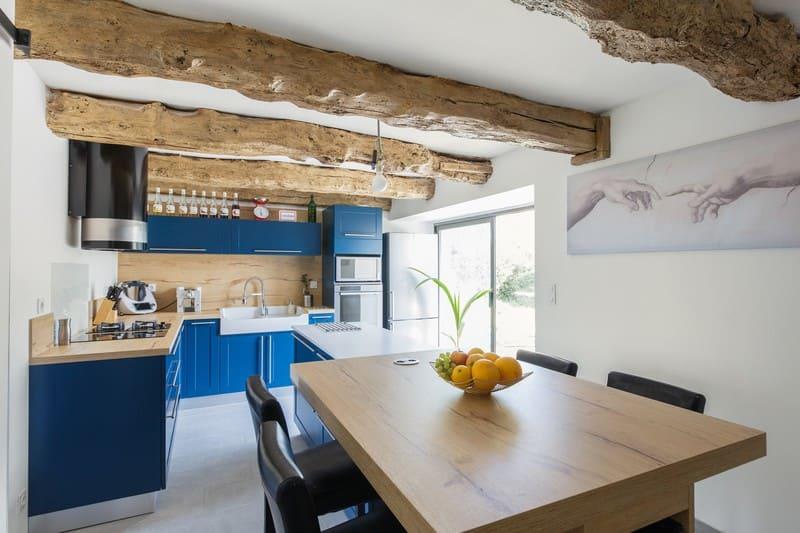 Cuisine en L blanche bois et bleue avec îlot central avec cave à vin intégrée| Raison Home - 2