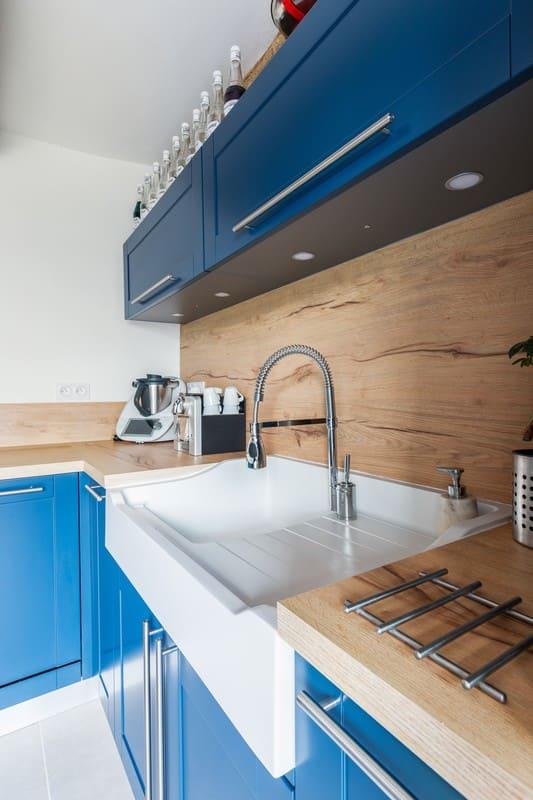 Cuisine en L blanche bois et bleue avec îlot central avec cave à vin intégrée| Raison Home - 5