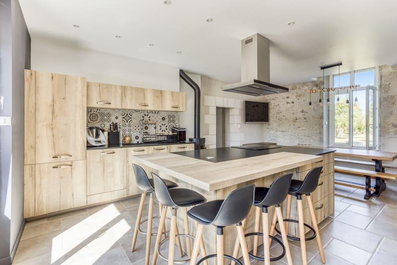 Cuisine en bois avec grand îlot central et espace repas par Eddy Blatrix - 1