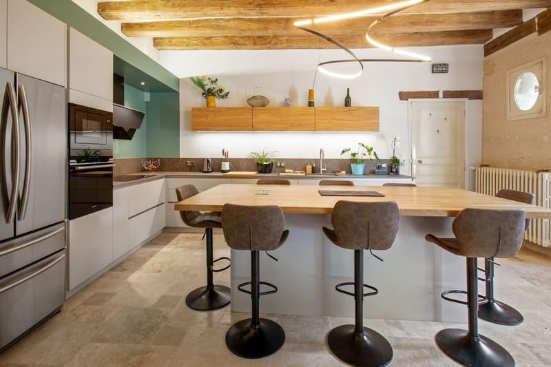 Cuisine ouverte bois et Dekton avec cheminée et poutres | Raison Home - 2