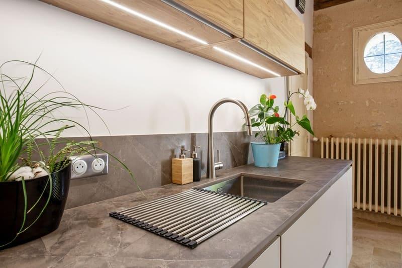 Cuisine ouverte bois et Dekton avec cheminée et poutres | Raison Home - 7