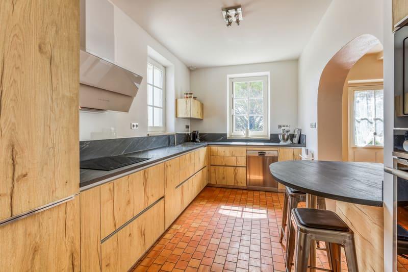Cuisine en L façade en bois et crédence noire avec petit coin repas par PASCAL LAURENCE | Raison Home - 1