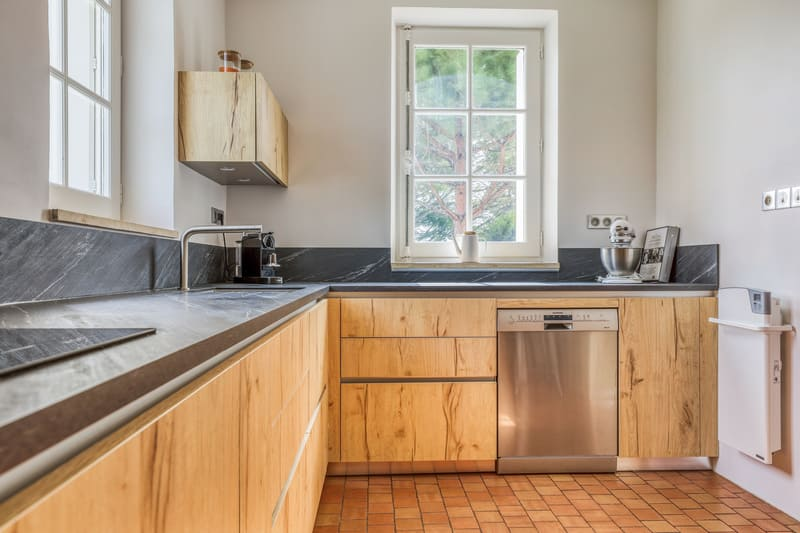 Cuisine en L façade en bois et crédence noire avec petit coin repas par PASCAL LAURENCE | Raison Home - 5