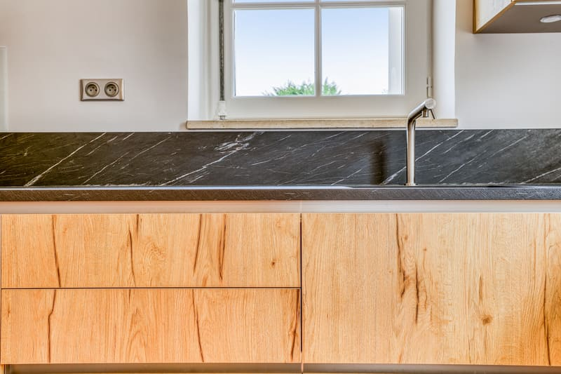 Cuisine en L façade en bois et crédence noire avec petit coin repas par PASCAL LAURENCE | Raison Home - 6