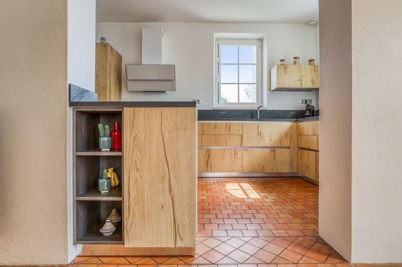 Cuisine en L façade en bois et crédence noire avec petit coin repas par PASCAL LAURENCE | Raison Home - 7