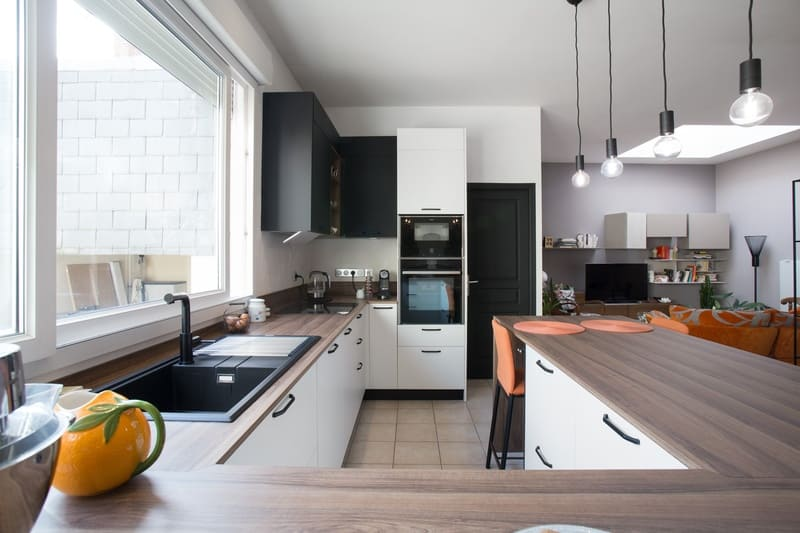 Cuisine blanche et bois façade noire avec îlot en U et coin repas par Pascal LAURENCE | Raison Home  - 1