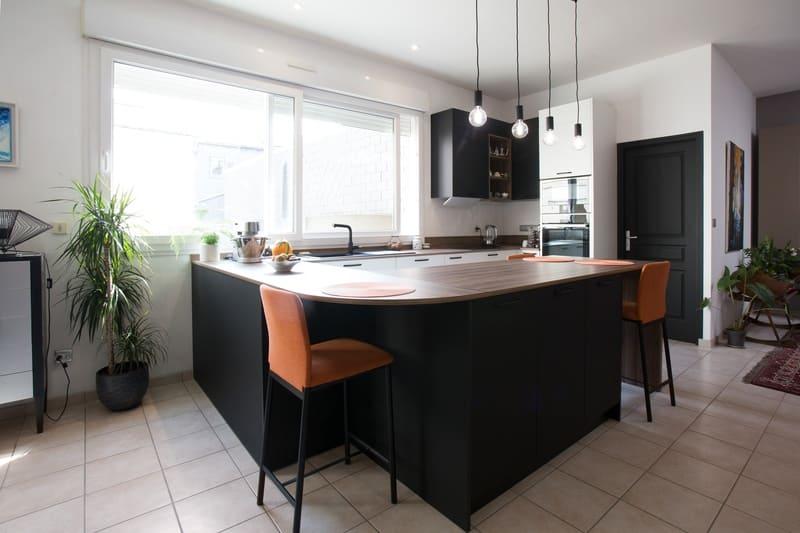 Cuisine blanche et bois façade noire avec îlot en U et coin repas par Pascal LAURENCE | Raison Home  - 2