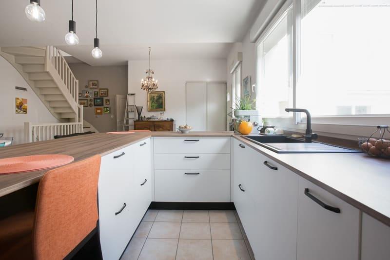 Cuisine blanche et bois façade noire avec îlot en U et coin repas par Pascal LAURENCE | Raison Home  - 4