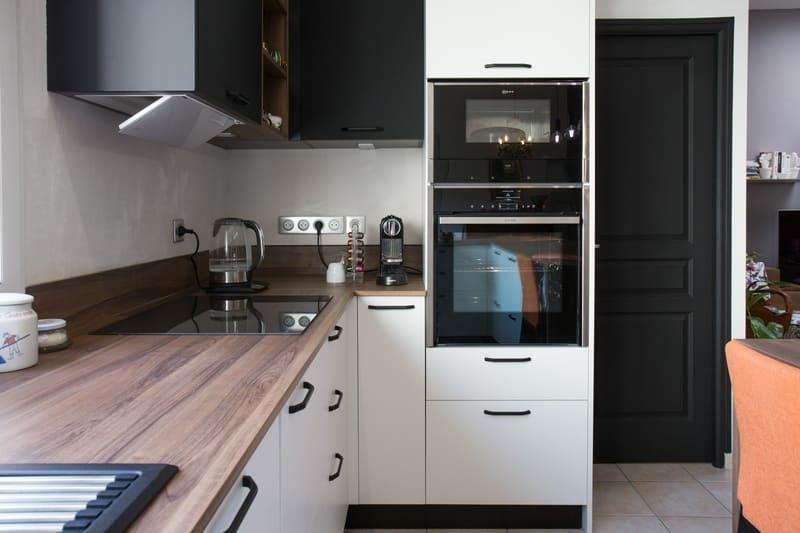 Cuisine blanche et bois façade noire avec îlot en U et coin repas par Pascal LAURENCE | Raison Home  - 7