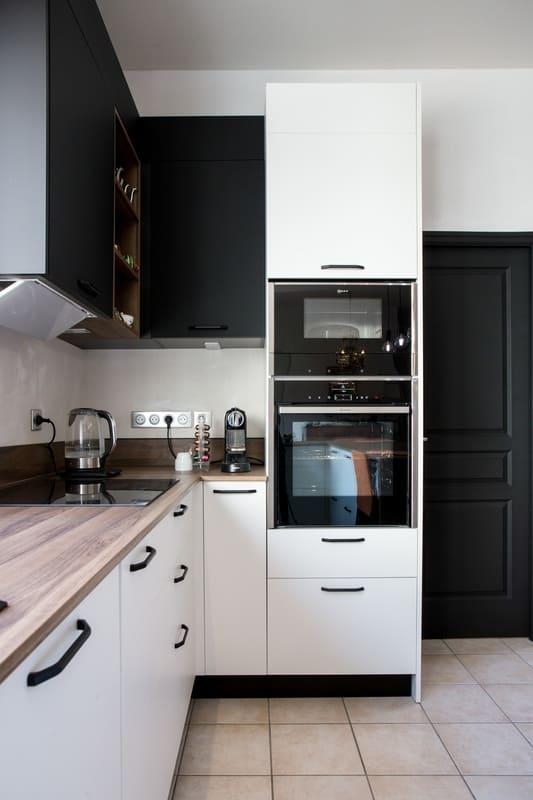 Cuisine blanche et bois façade noire avec îlot en U et coin repas par Pascal LAURENCE | Raison Home  - 8