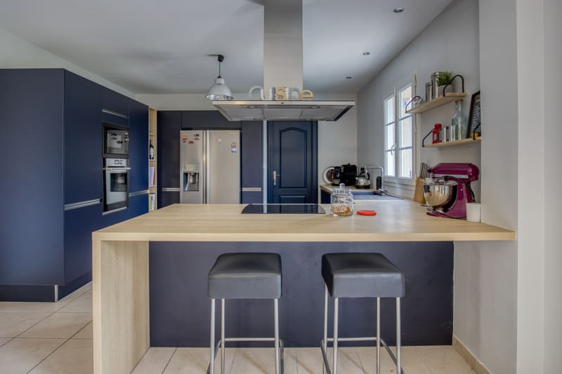 Cuisine ouverte bleue et bois avec îlot par Romain CARBONNEL| Raison Home - 1