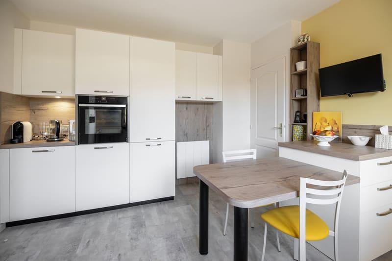 Cuisine aménagée blanche et bois avec petit coin repas par MAZZOCCO | Raison Home - 1
