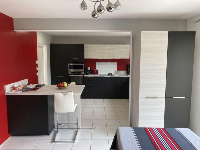 Cuisine rouge noire et bois avec îlot par Sébastien Guesdon | Raison Home - 1