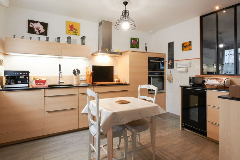 Cuisine ouverte noire et bois en couloir avec verrière | Raison Home - 2