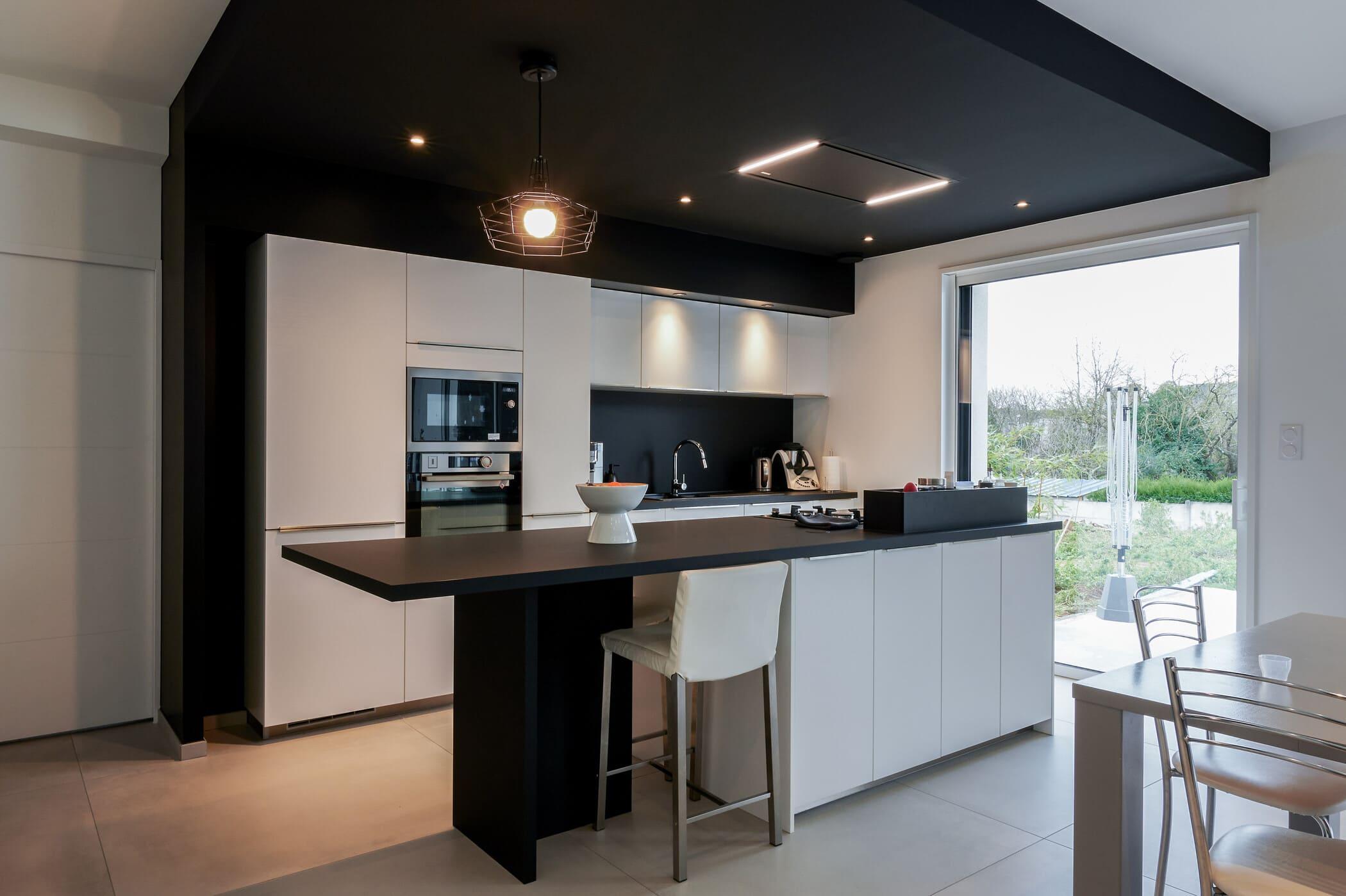 Cuisine ouverte design noire et blanche avec îlot central | Raison Home - 1