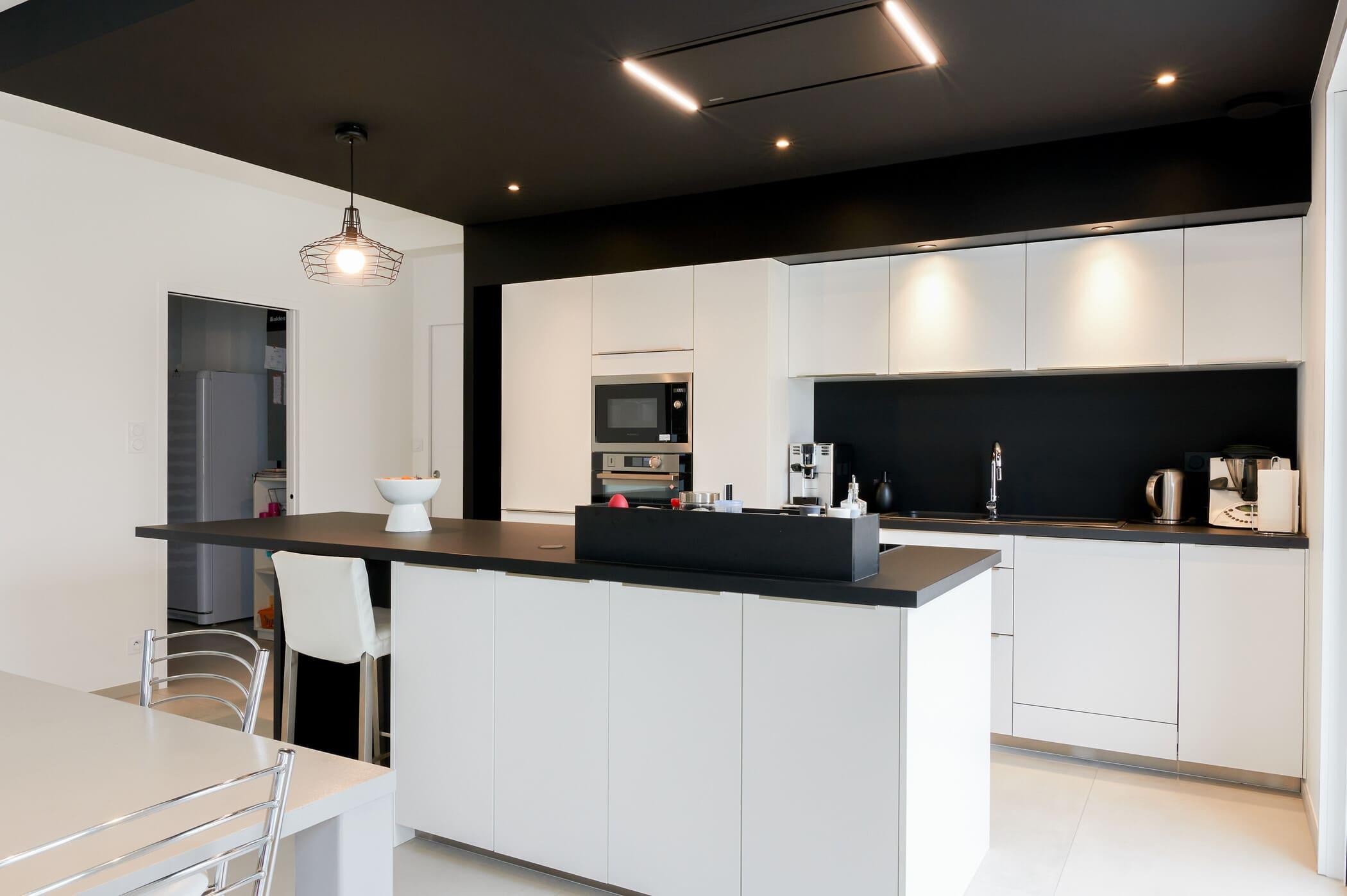 Cuisine ouverte design noire et blanche avec îlot central | Raison Home - 3