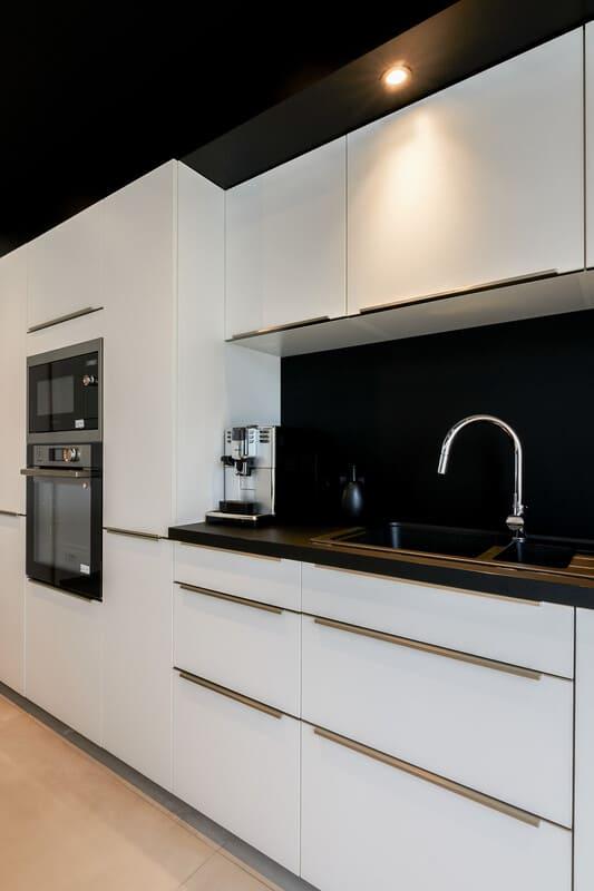 Cuisine ouverte design noire et blanche avec îlot central | Raison Home - 5