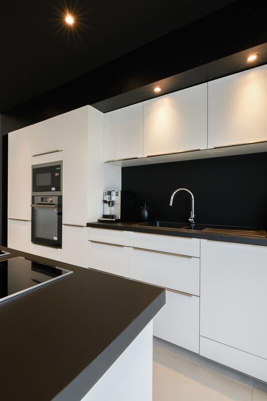Cuisine ouverte design noire et blanche avec îlot central | Raison Home - 7