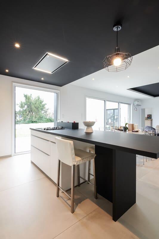 Cuisine ouverte design noire et blanche avec îlot central | Raison Home - 4