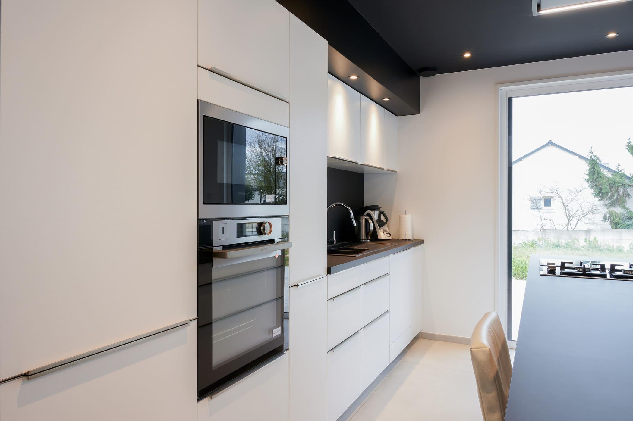 Cuisine ouverte design noire et blanche avec îlot central | Raison Home - 6