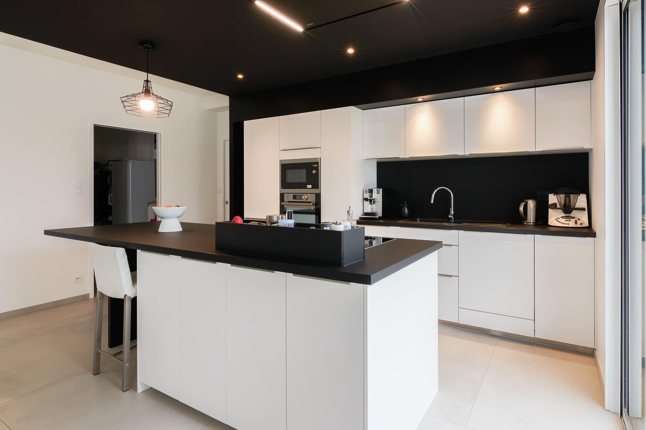 Cuisine ouverte design noire et blanche avec îlot central | Raison Home - 8