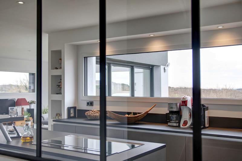 Cuisine aménagée grise avec verrière par Gérald JOUNOT | Raison Home - 2