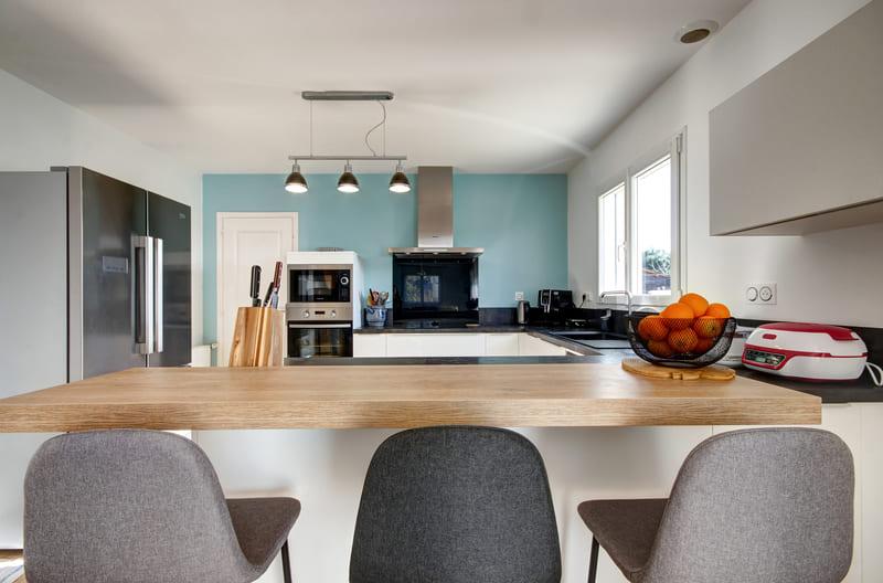 Cuisine ouverte blanche, bois et bleu ciel avec bar par Gérald JOUNOT | Raison Home - 1